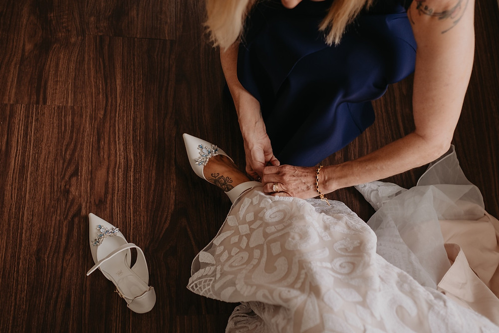 Bride putting on shoes before wedding ceremony. Photographed by Nicole Leanne Photography.