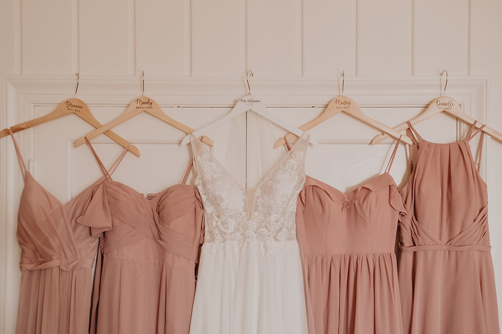 Hanging bridesmaid dresses with wedding dress. Photographed by Nicole Leanne Photography.