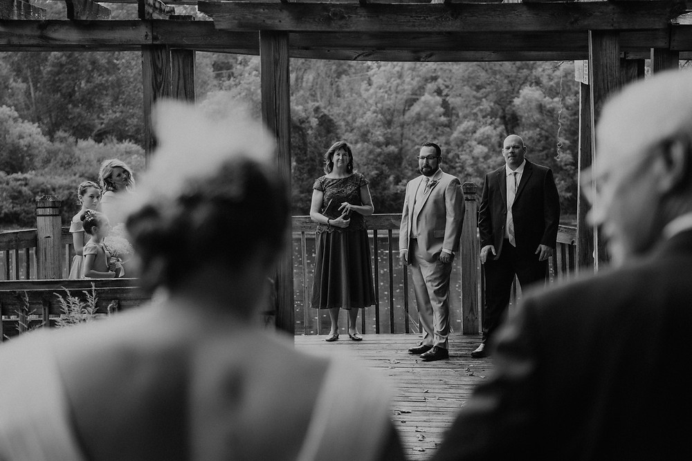 Groom sees bride for first time down aisle. Photographed by Nicole Leanne Photography.