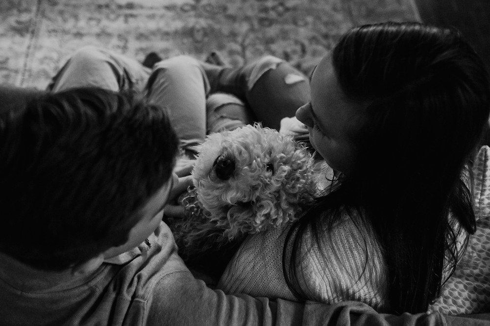Cuddling with dog during home photo session. Photographed by Nicole Leanne Photography.