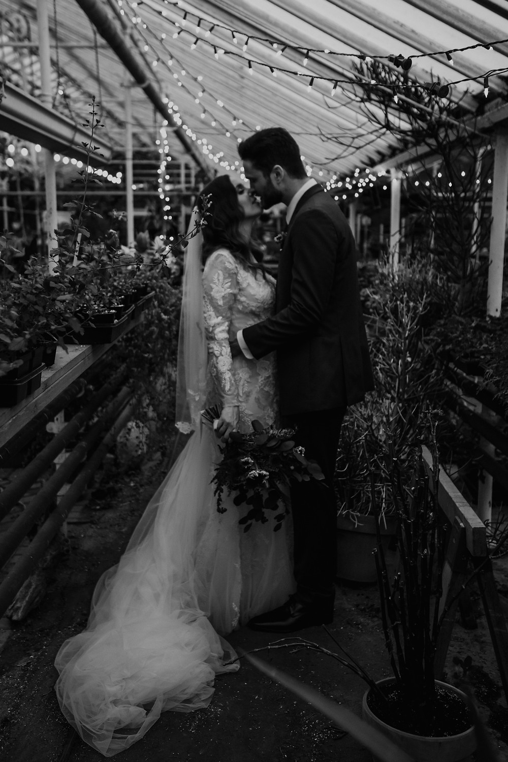 String lights hun in greenhouse for wedding ceremony. Photographed by Nicole Leanne Photography.