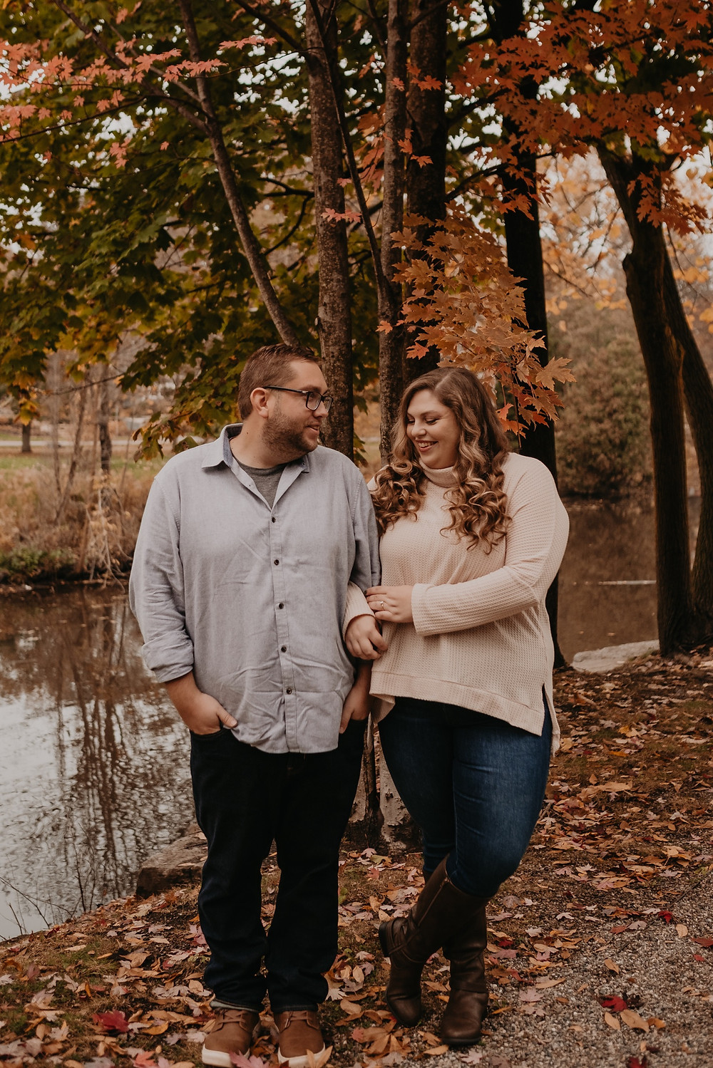 Couple walking through park with fall colors. Photographed by Nicole Leanne Photography.
