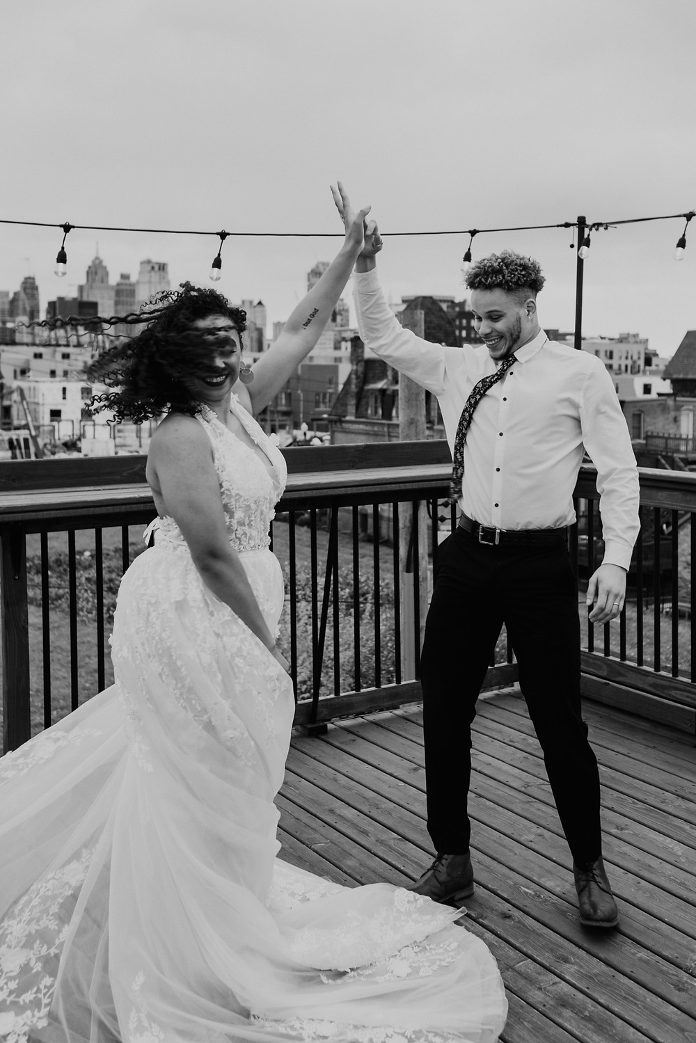 Couple dancing outside under patio lights with view of Detroit skyline. Photographed by Nicole Leanne Photography.