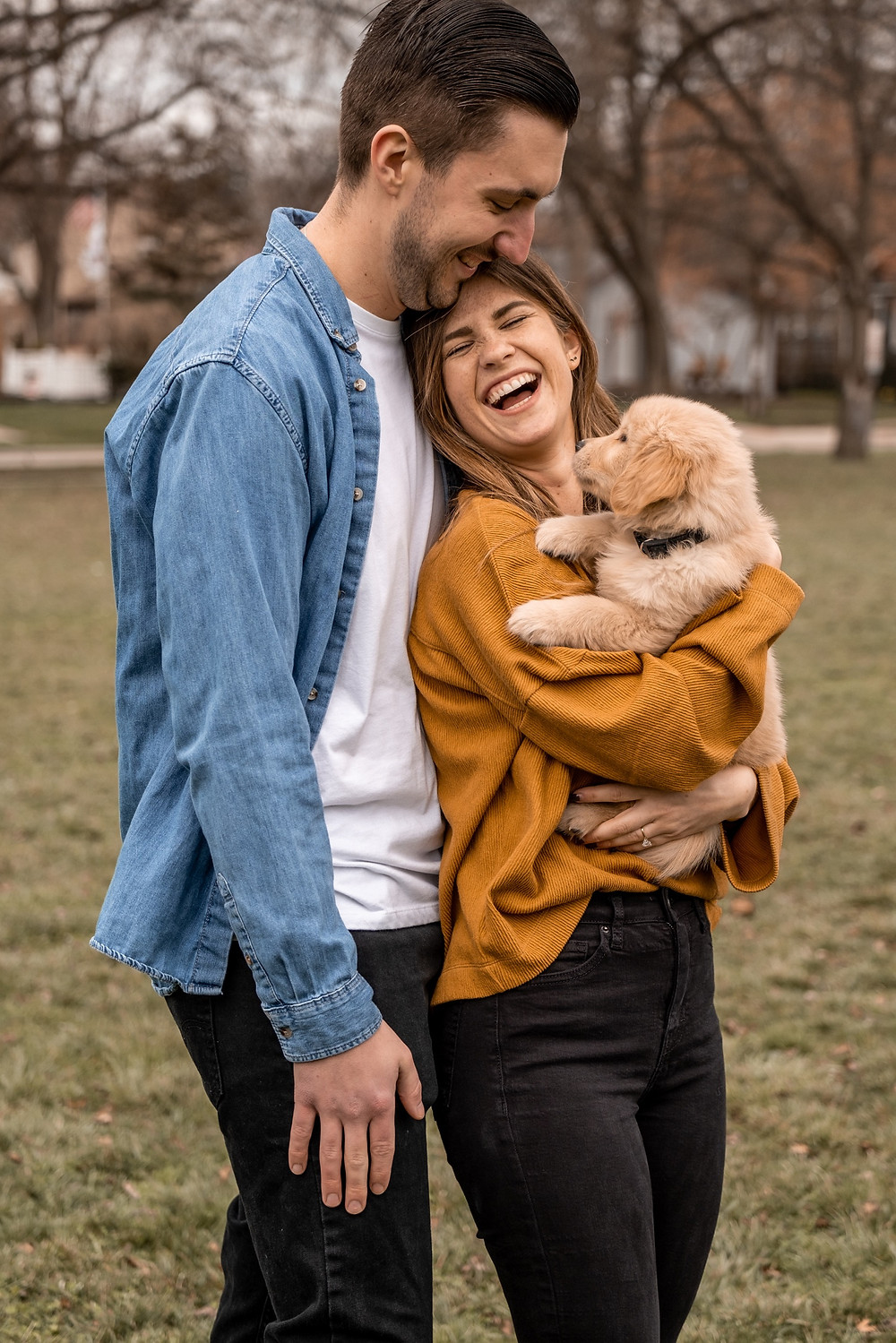 Couple holding puppy at park after proposal in Royal Oak Michigan. Photographed by Nicole Leanne Photography