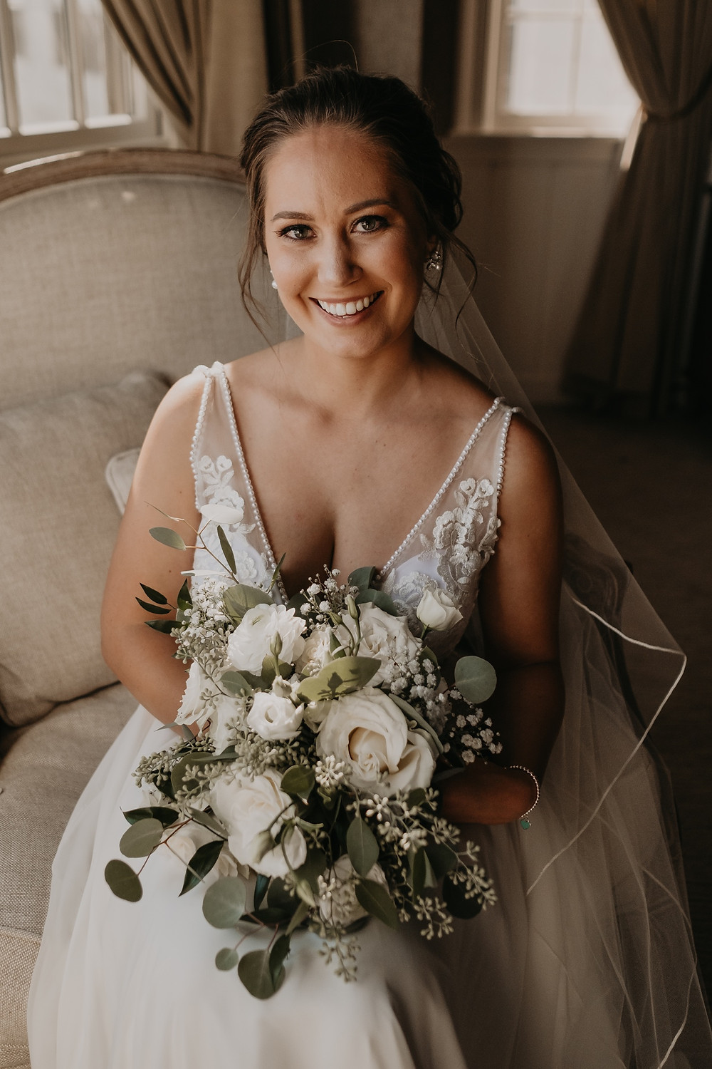 Bridal portrait with bride's bouquet of white roses and greenery