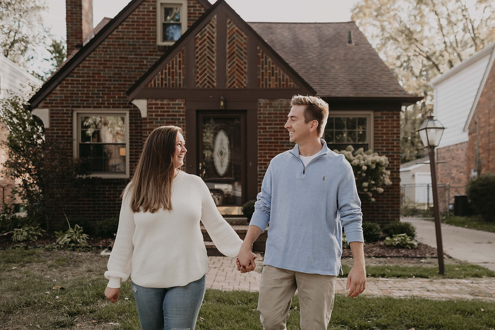 Couple holding hands walking outside home in Metro Detroit. Photographed by Nicole Leanne Photography.