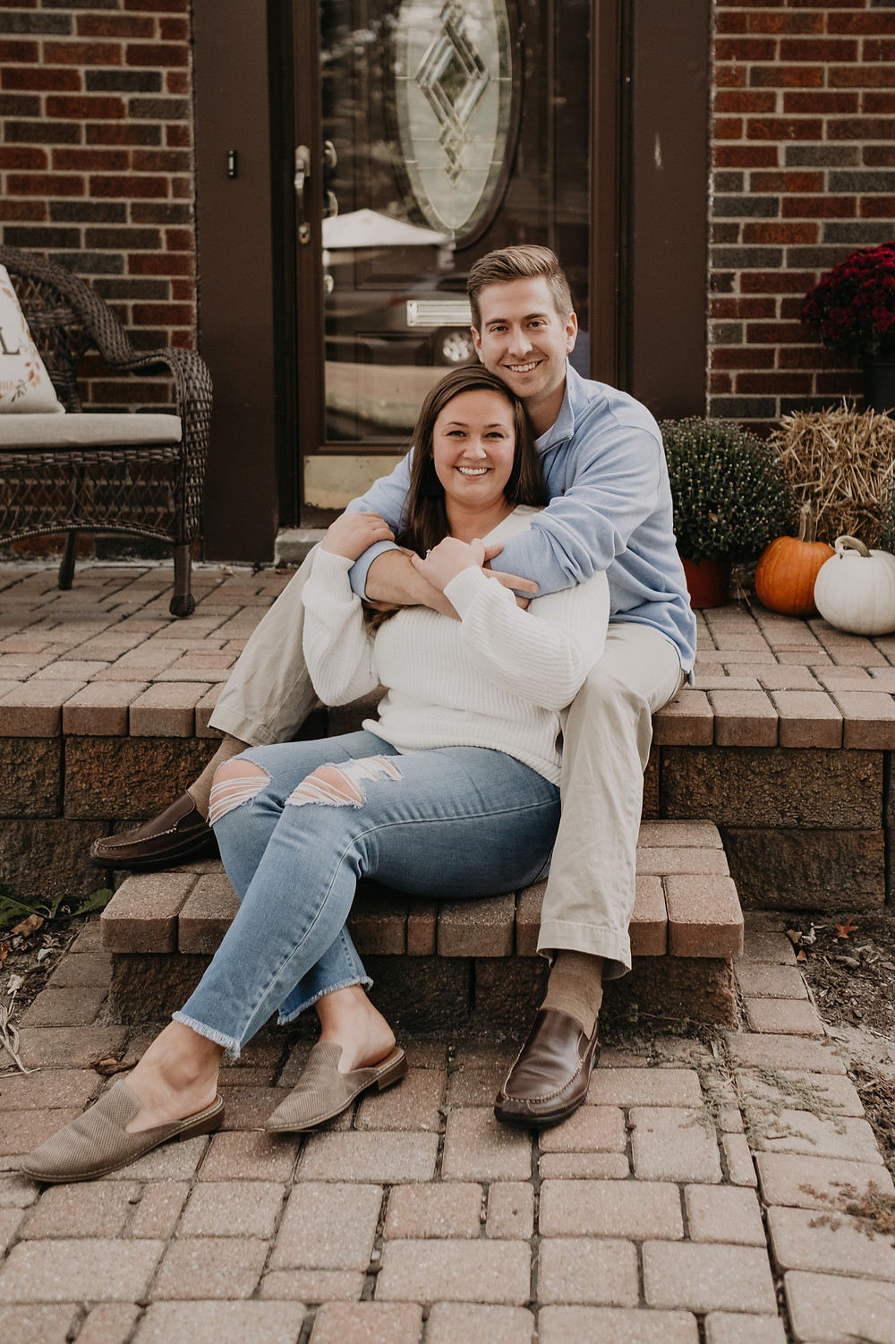 Couple sitting on porch steps at home engagement session in Metro Detroit. Photographed by Nicole Leanne Photography.