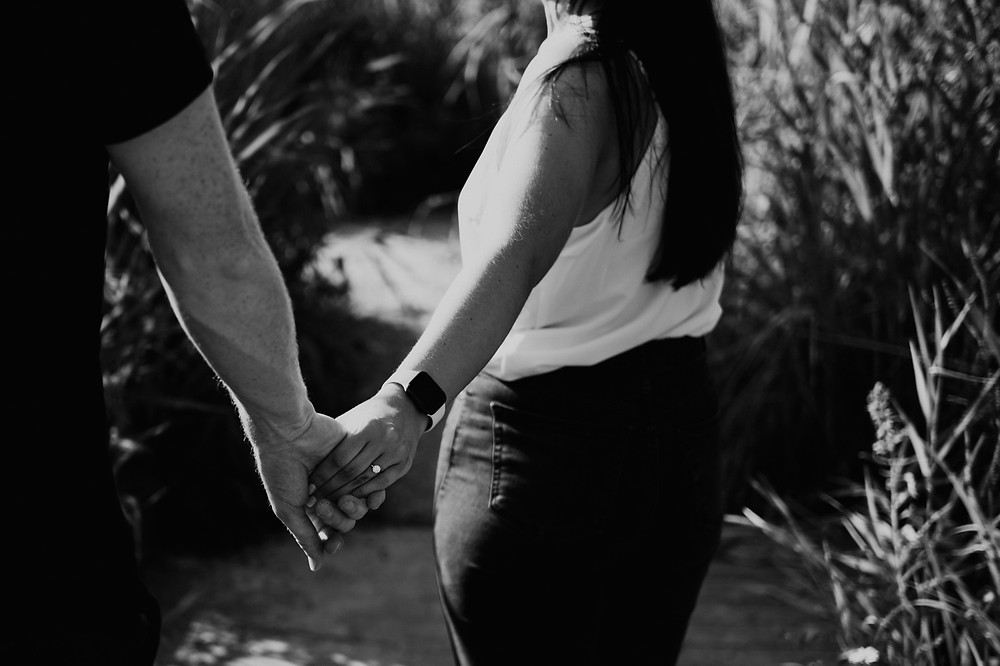Woman leading man through woods after engagement. Photographed by Nicole Leanne Photography