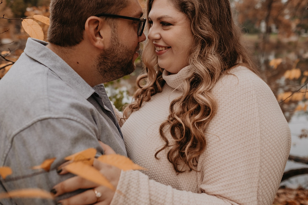 Engaged couple embracing during fall engagement session in Metro Detroit park. Photographed by Nicole Leanne Photography.
