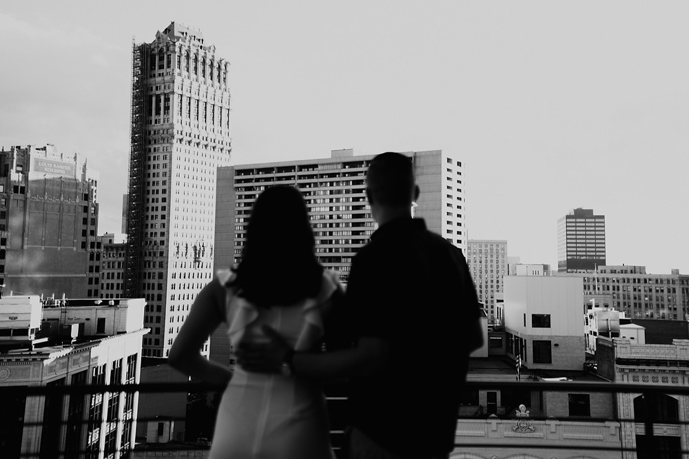 Black and white photo of couple looking out at Detroit skyline. Photographed by Nicole Leanne Photography.