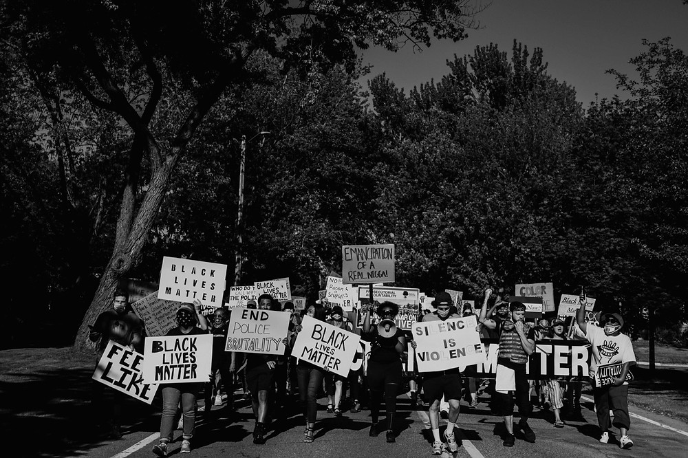 End police brutality and black lives matter protest signs through Berkley Michigan
