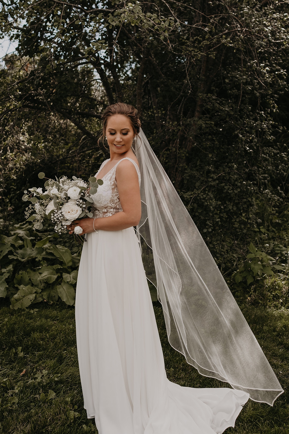 Bride with veil and floral bouquet. Photographed by Nicole Leanne Photography.