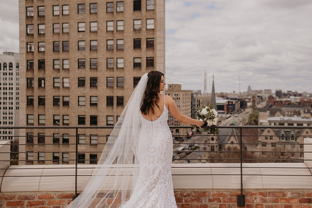 Bride with veil overlooking city of Detroit. Photographed by Nicole Leanne Photography.