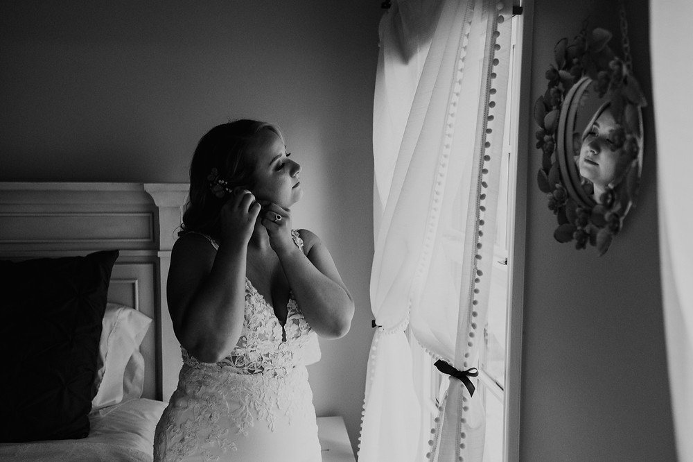 Bride putting on wedding jewelry before ceremony. Photographed by Nicole Leanne Photography.