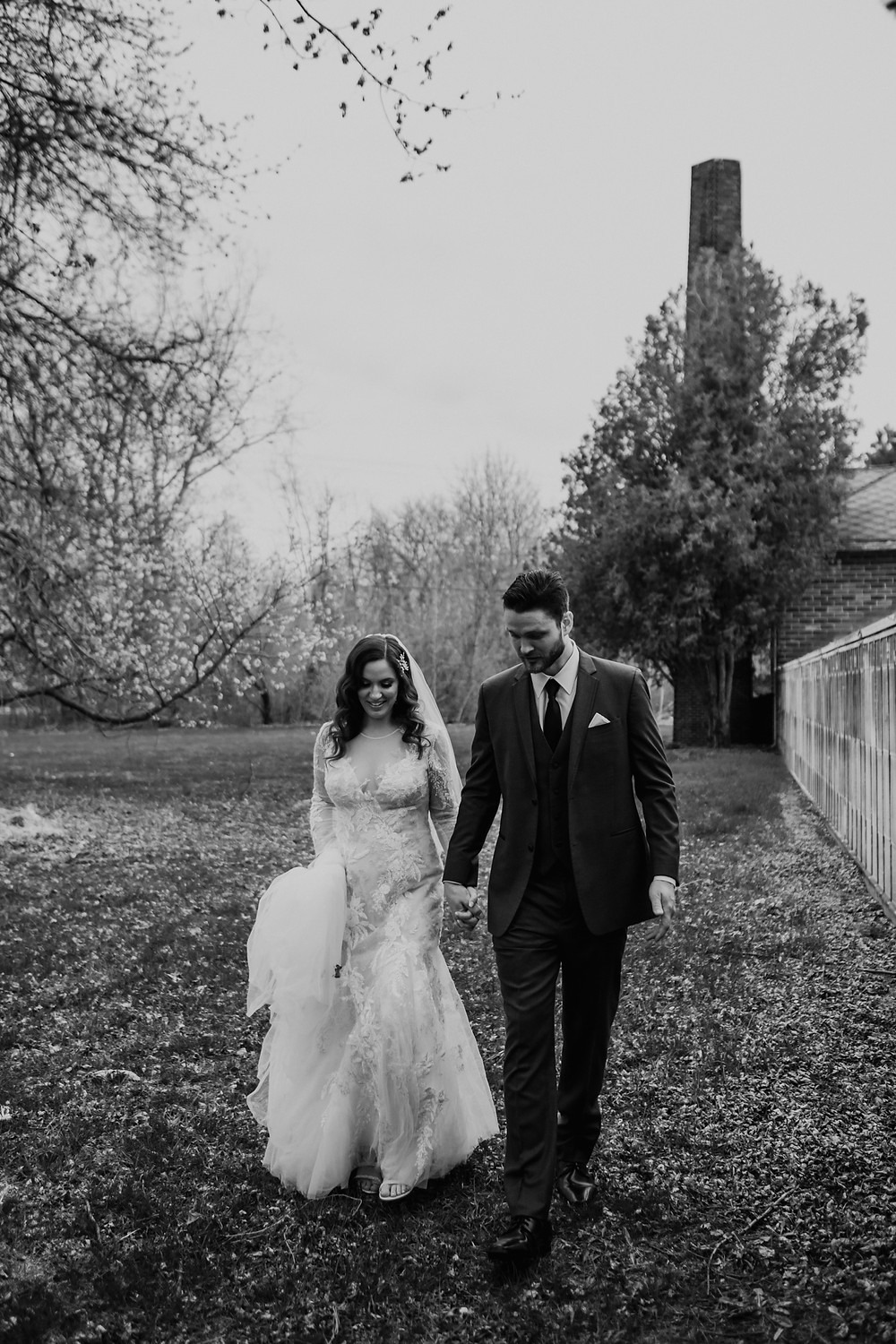 Black and white Metro Detroit wedding photo of bride and groom in a field. Photographed by Nicole Leanne Photography.