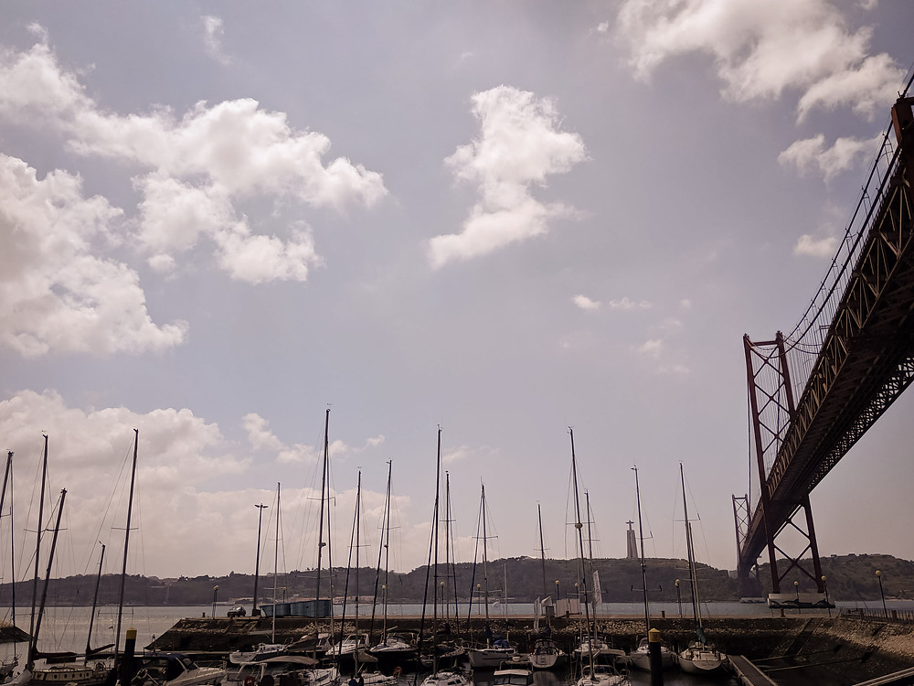 Lisbon marina with boats and mountains in the distance. Photographed by Nicole Leanne Photography.
