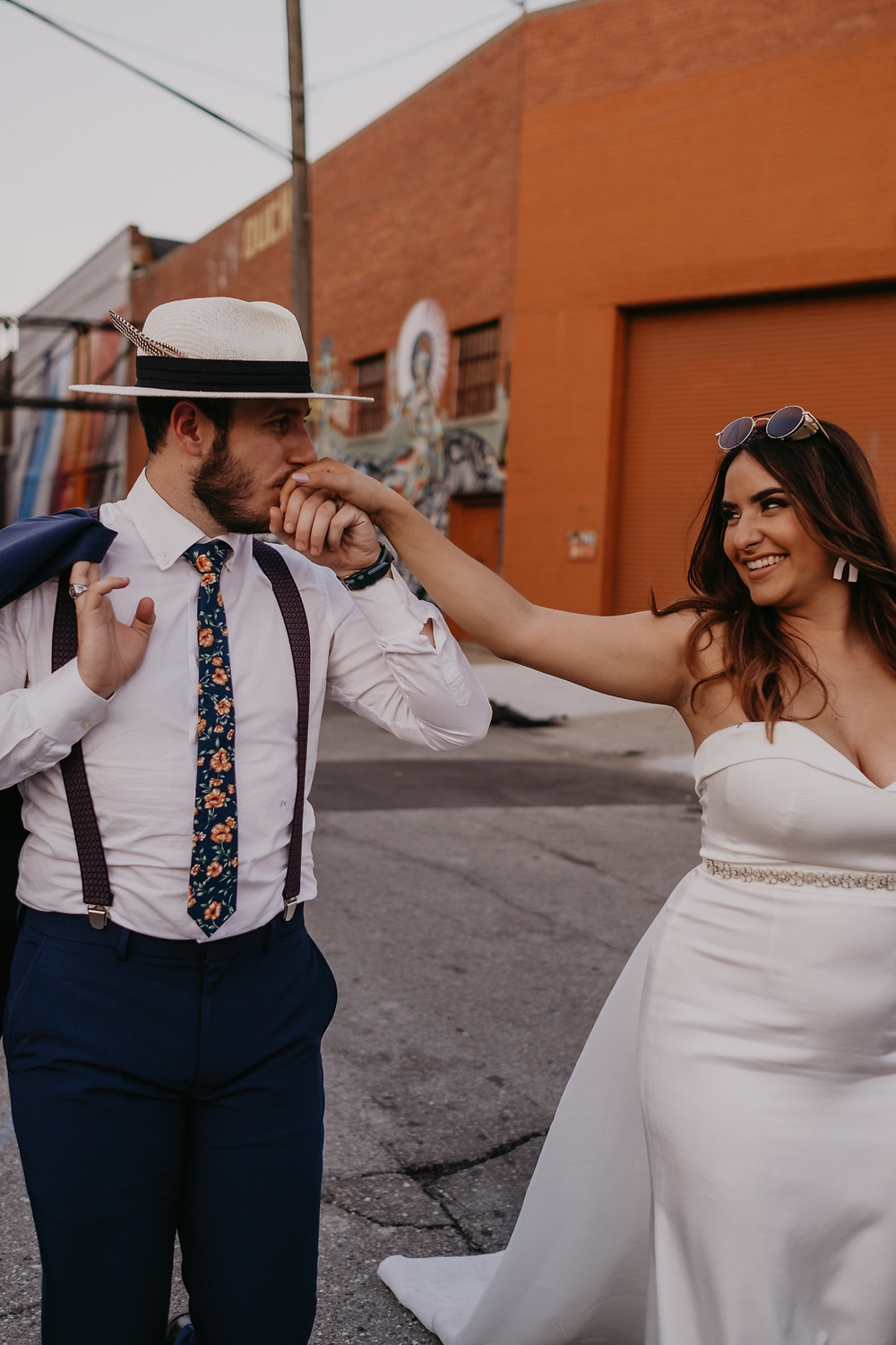 Bride and groom walking outside Eastern Market in Detroit. Photographed by Nicole Leanne Photography.