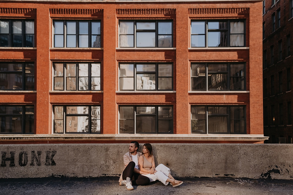 Downtown Detroit rooftop engagement photo with couple sitting. Photographed by Nicole Leanne Photography.