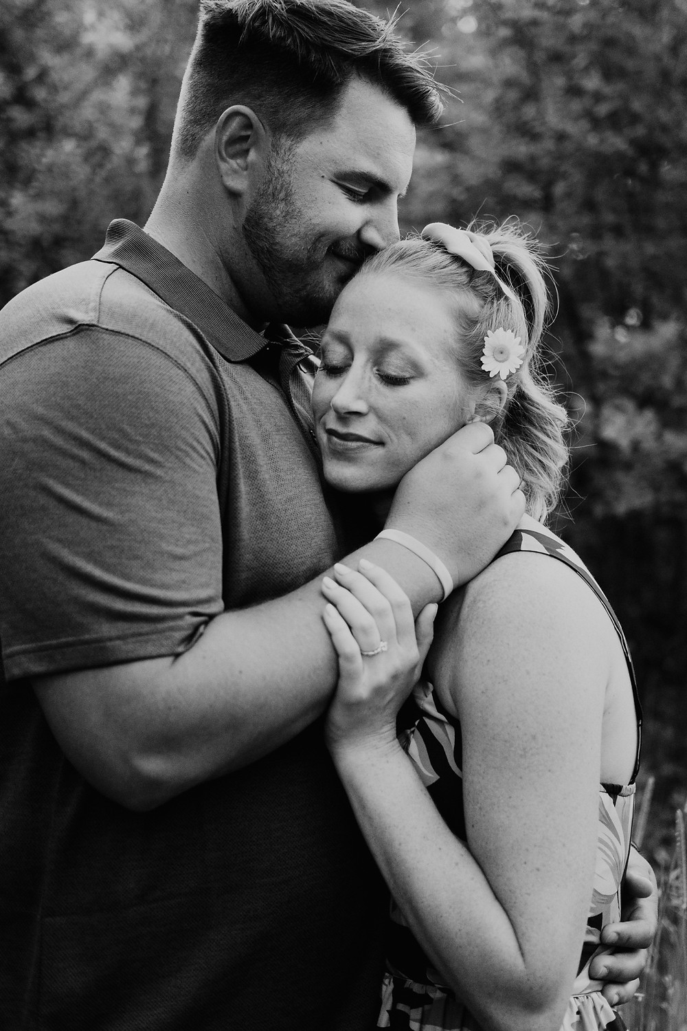 Couple embraces during engagement photos at park in Michigan. Photographed by Nicole Leanne Photography