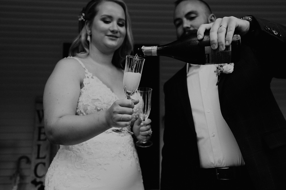 Bride and groom pouring champagne toast on wedding day. Photographed by Nicole Leanne Photography.