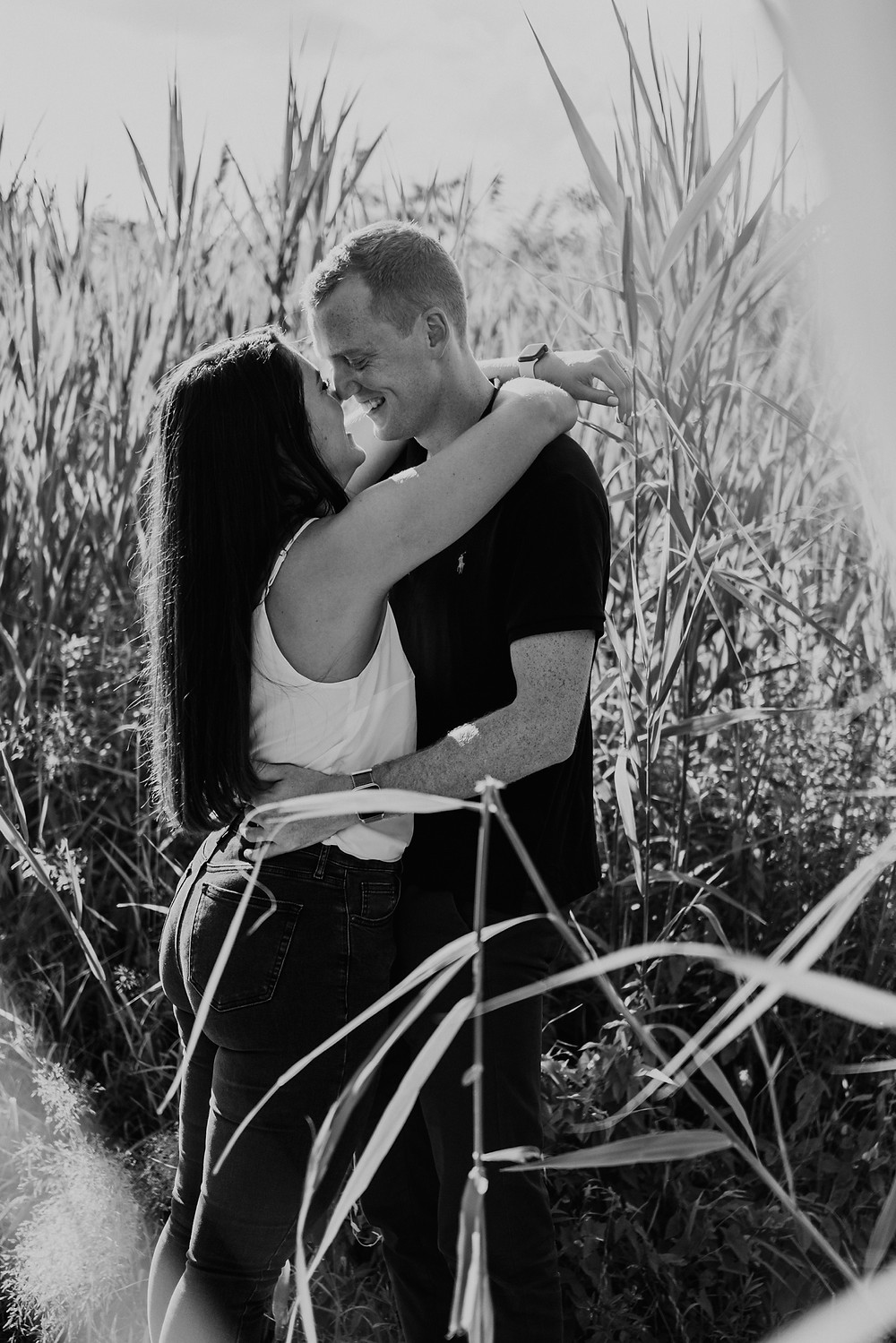 Couple posing for engagement photos in wooded field. Photographed by Nicole Leanne Photography