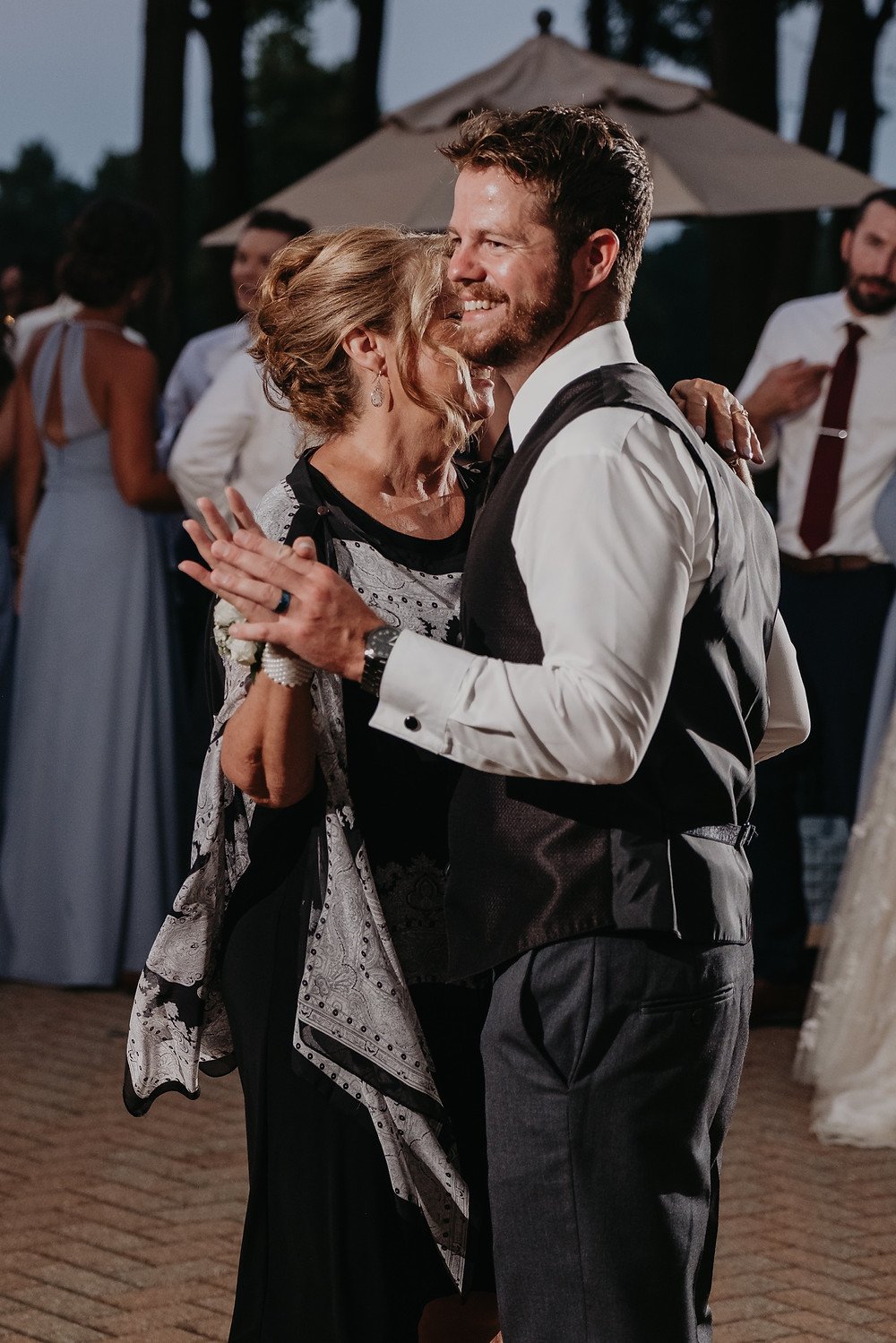 Mother of the groom dancing at wedding reception with groom. Photographed by Nicole Leanne Photography.