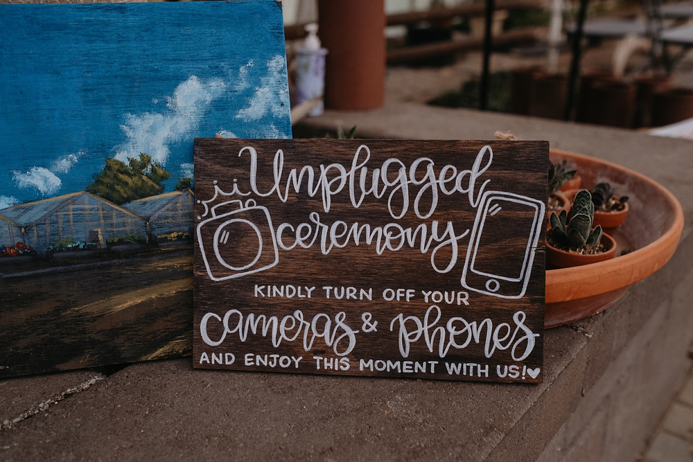Unplugged ceremony sign asking guests to turn off phones. Photographed by Nicole Leanne Photography.