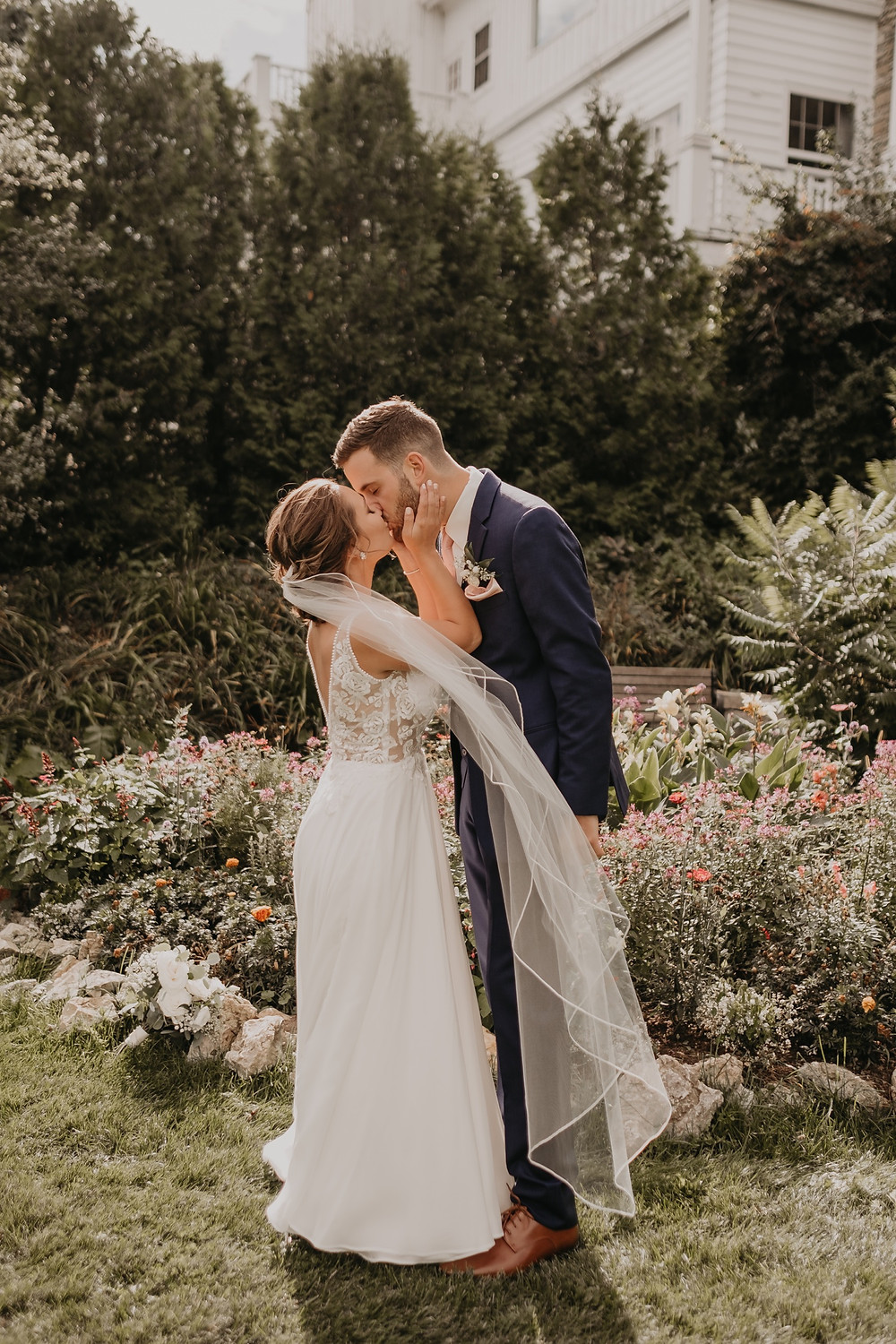 Bride and groom in flower garden for wedding photos. Photographed by Nicole Leanne Photography.