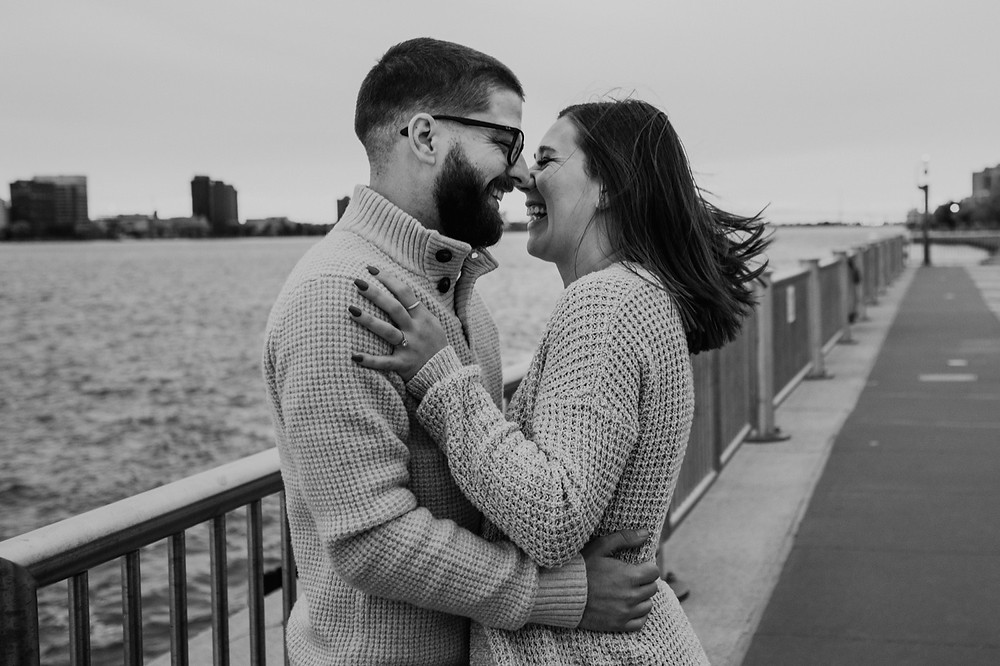 Black and white photos of couple laughing during engagement photos at Detroit Riverwalk. Photography by Nicole Leanne Photography