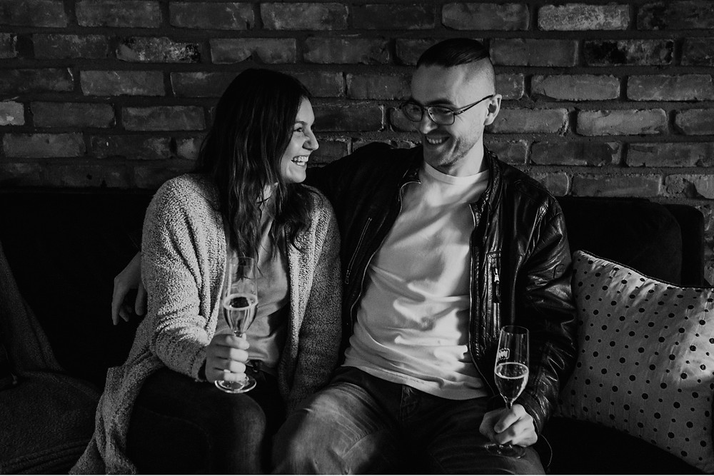 Black and white photo of couple relaxing at home for engagement session. Photographed by Nicole Leanne Photography.