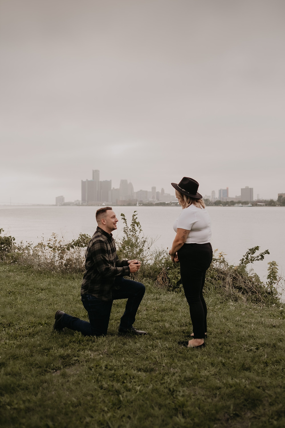 Man proposing on one knee with Detroit river in background. Photographed by Nicole Leanne Photography.