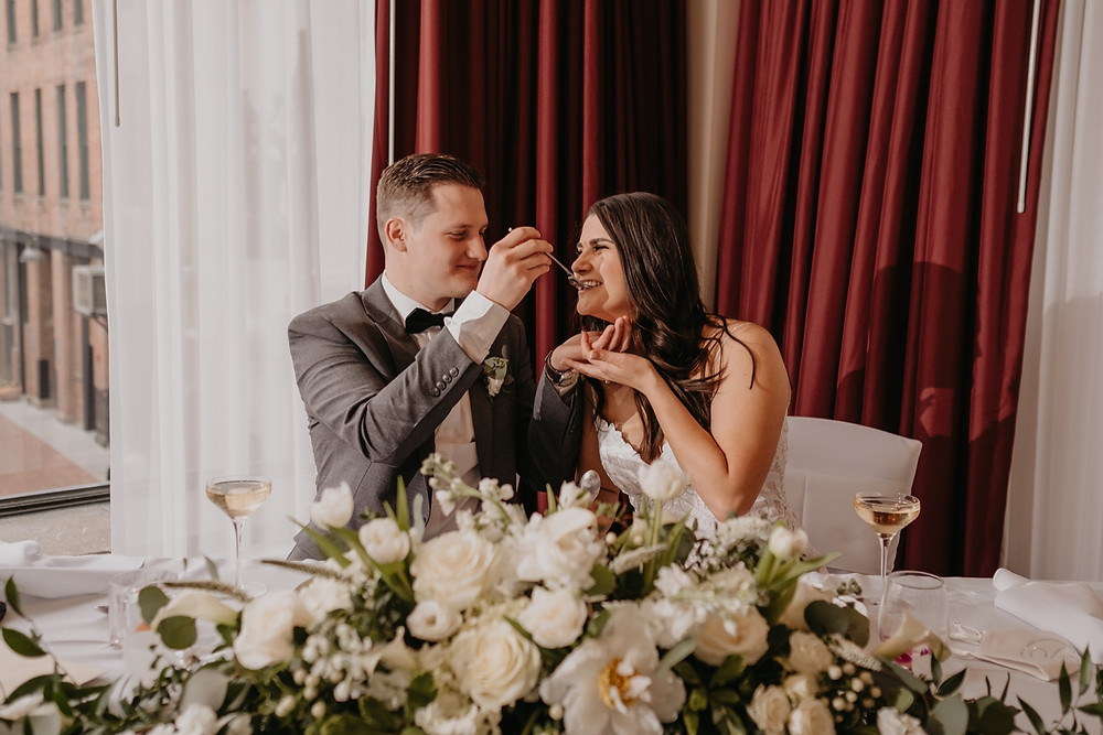 Bride and groom feeding wedding cake to each other