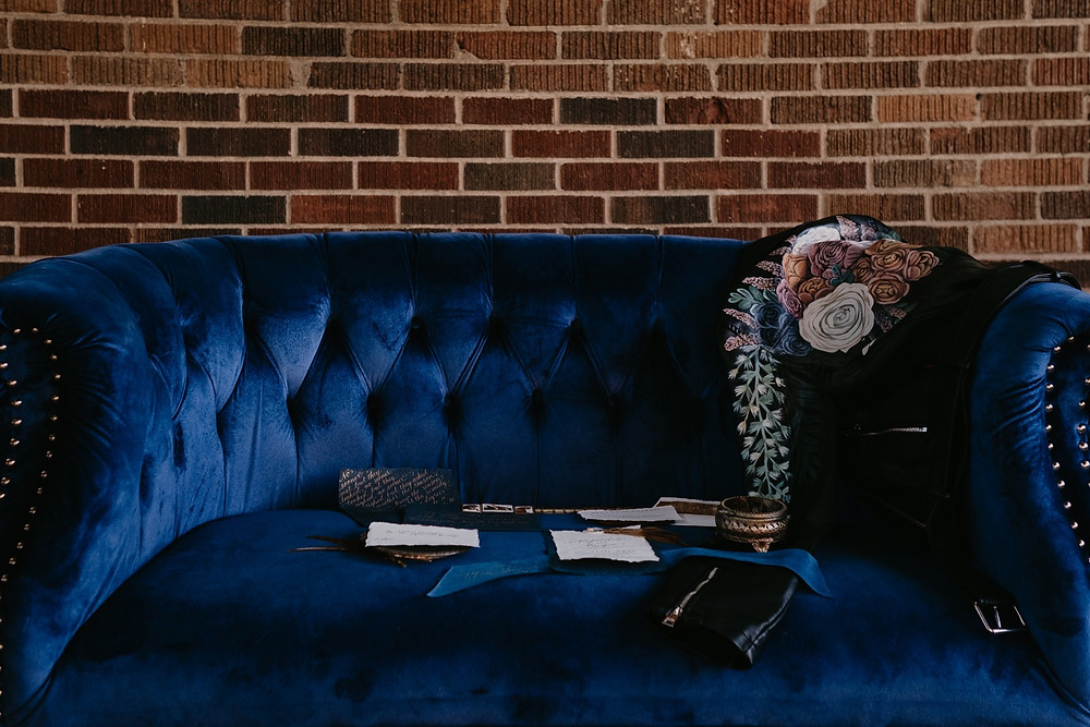 Wedding details on blue velvet couch. Photographed by Nicole Leanne Photography.