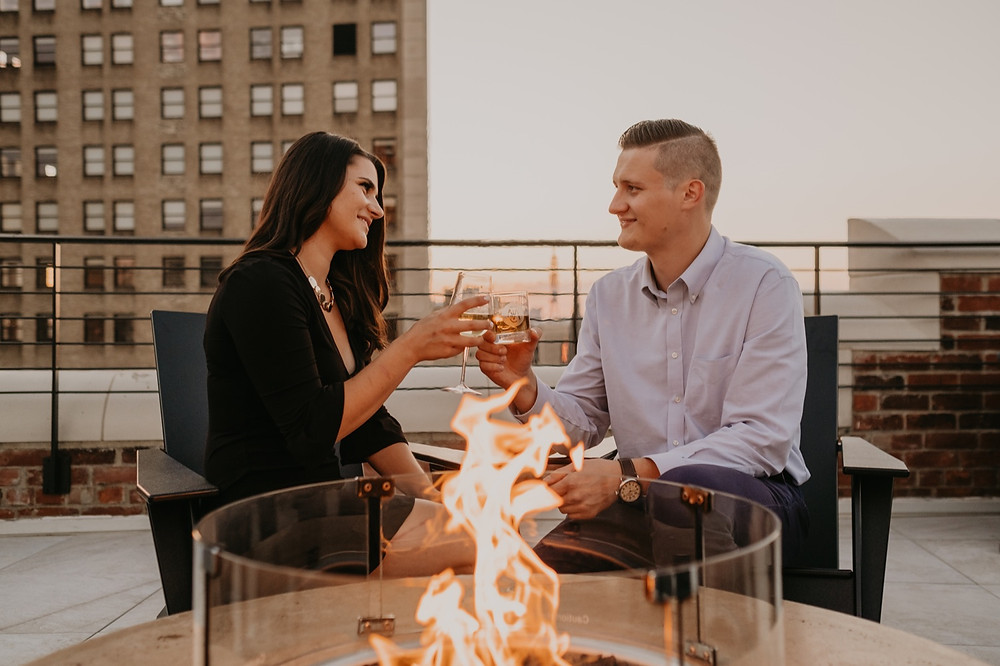 Couple sharing drink with fire pit on rooftop in Downtown Detroit. Photographed by Nicole Leanne Photography.