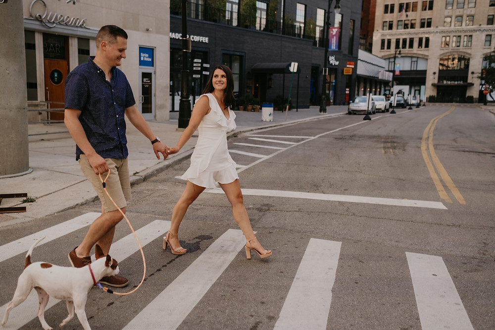 Downtown Detroit engaged couple walking with dog. Photographed by Nicole Leanne Photography.