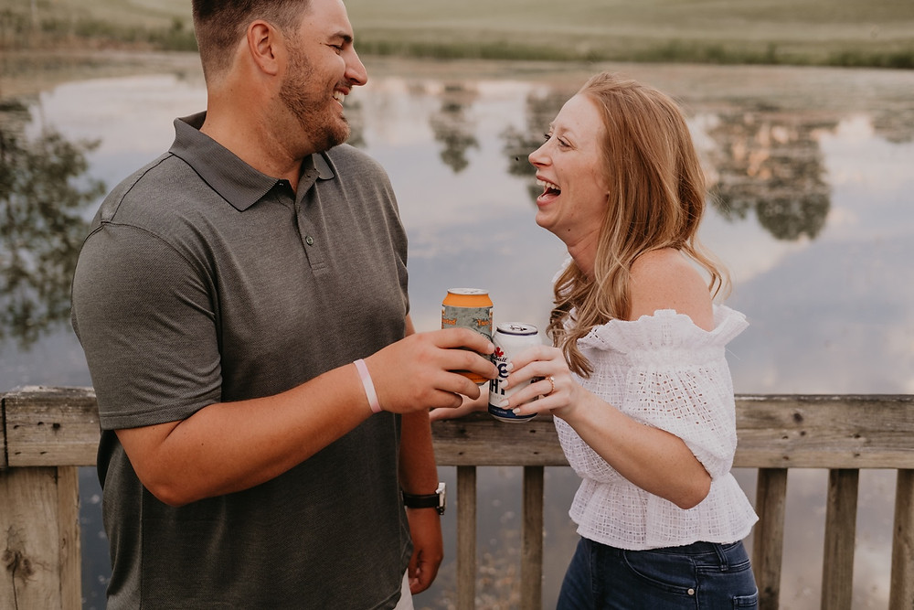 Sharing beers at golf course during engagement session. Photographed by Nicole Leanne Photography