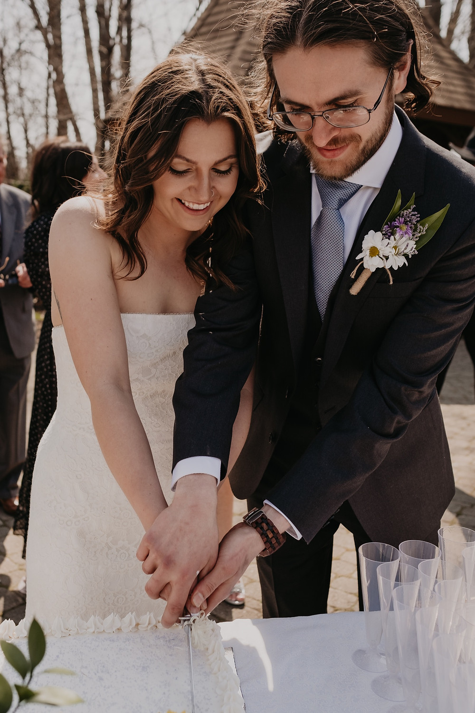 Bride and groom cutting wedding cake at park wedding in Metro Detroit.