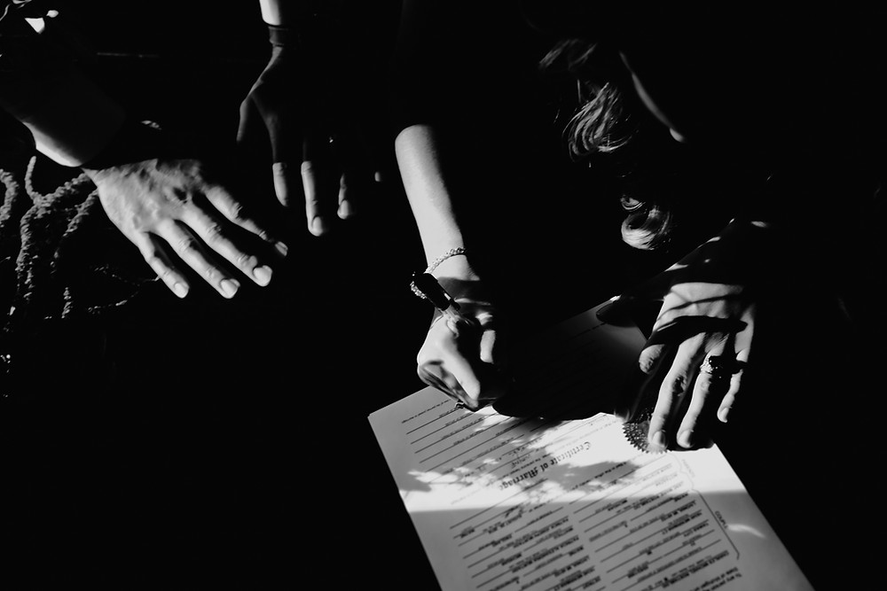 Black an white image of couple signing marriage license. Photographed by Nicole Leanne Photography.
