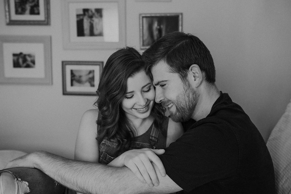 Black and white photo of couple on couch during home lifestyle photography session.