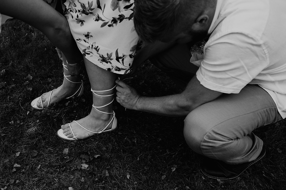 Groom fastening Bride's shoe lace. Photographed by Nicole Leanne Photography.