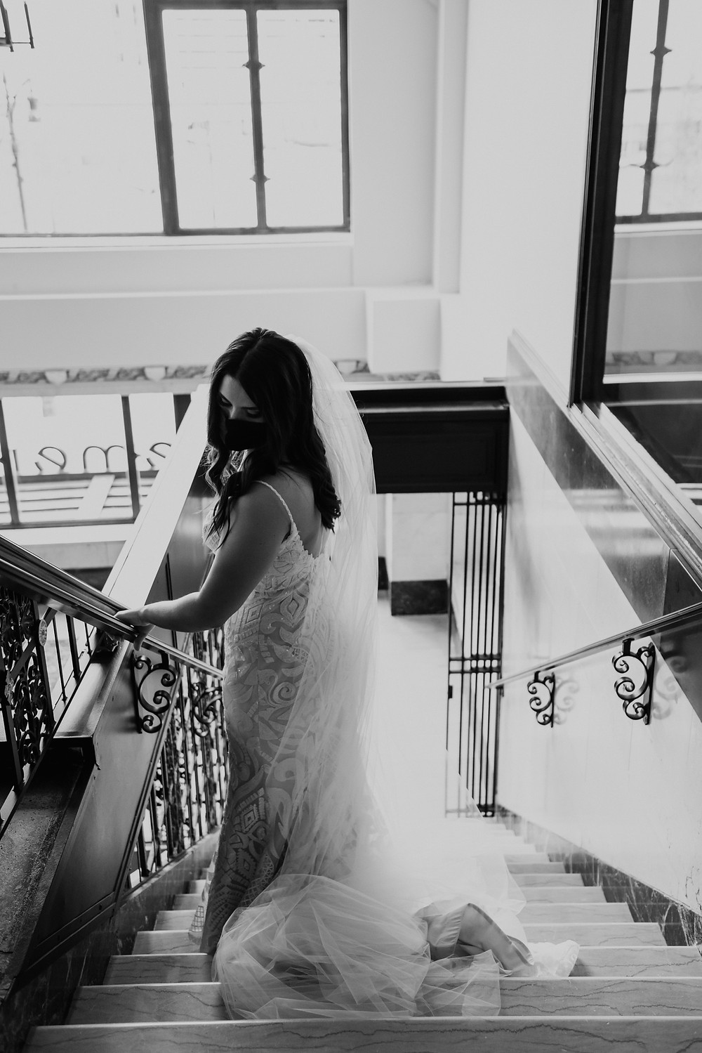 Bride walking down stairs with wedding dress and train. Photographed by Nicole Leanne Photography.