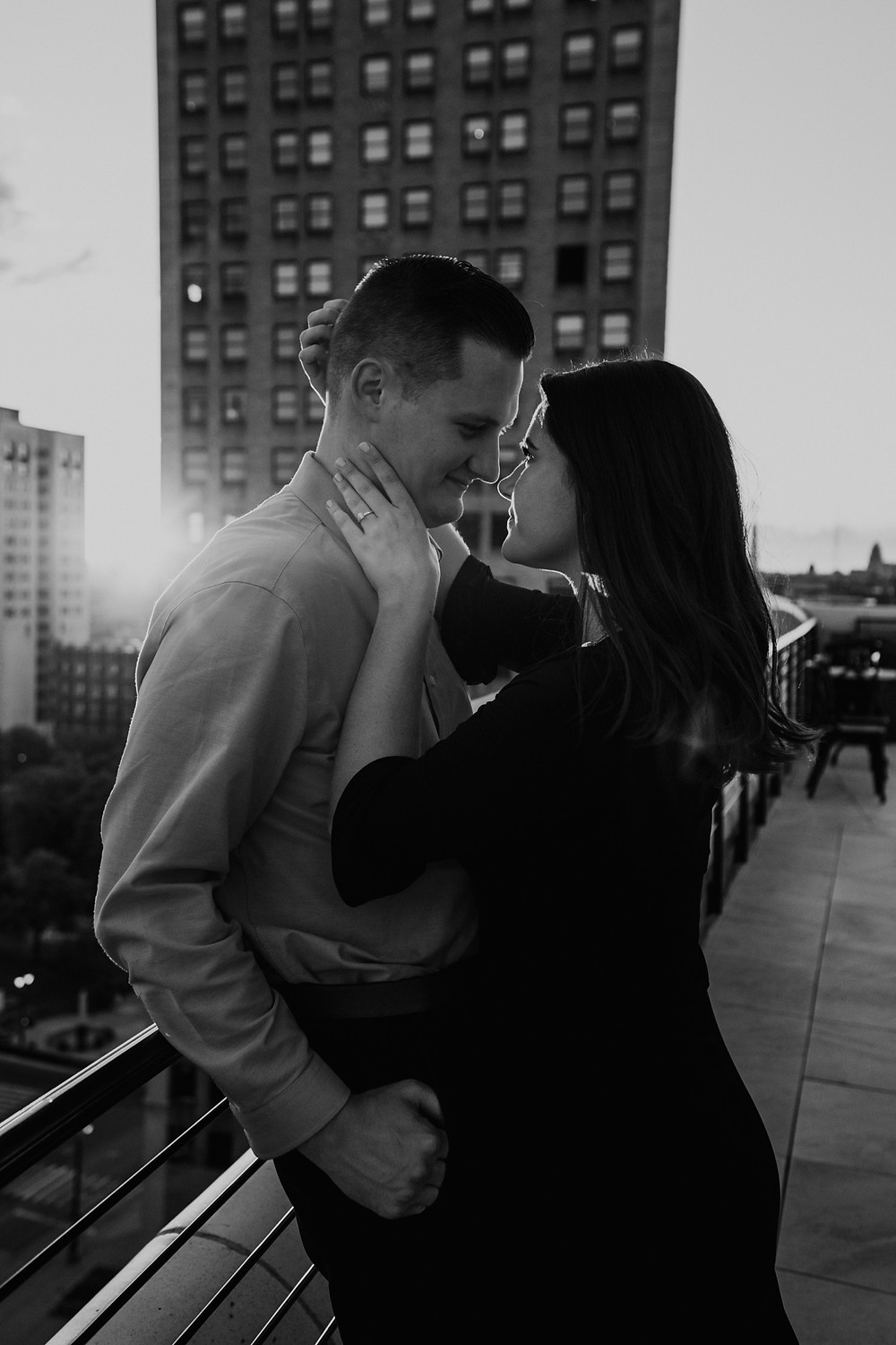 Black and white photo of couple at sunset on the rooftop in Downtown Detroit.