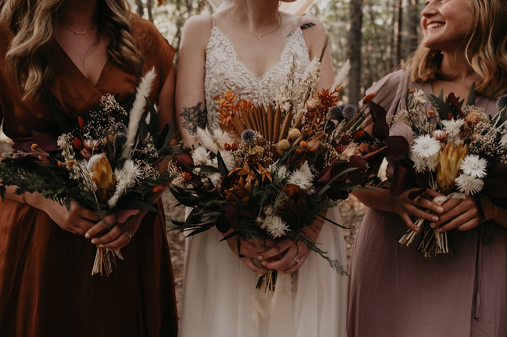 Bride and bridesmaids holding dried wedding bouquets crafted by The Lost Forty
