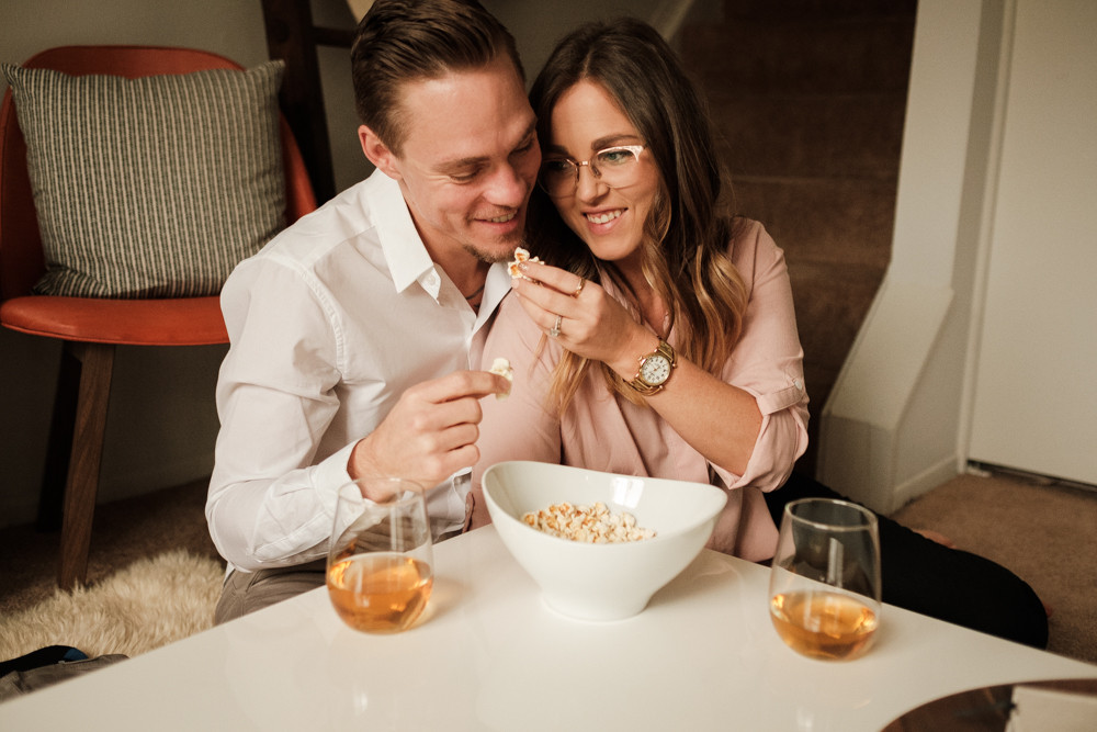 Couple eating popcorn at home. Photographed by Nicole Leanne Photography.