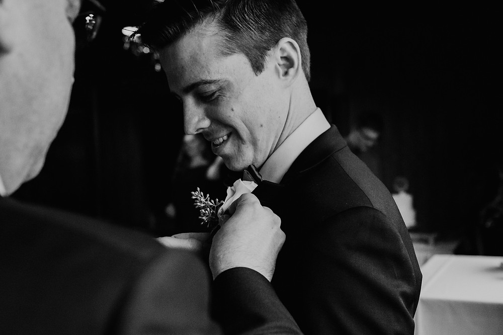 Groom receiving boutonniere on wedding day. Photographed by Nicole Leanne Photography.