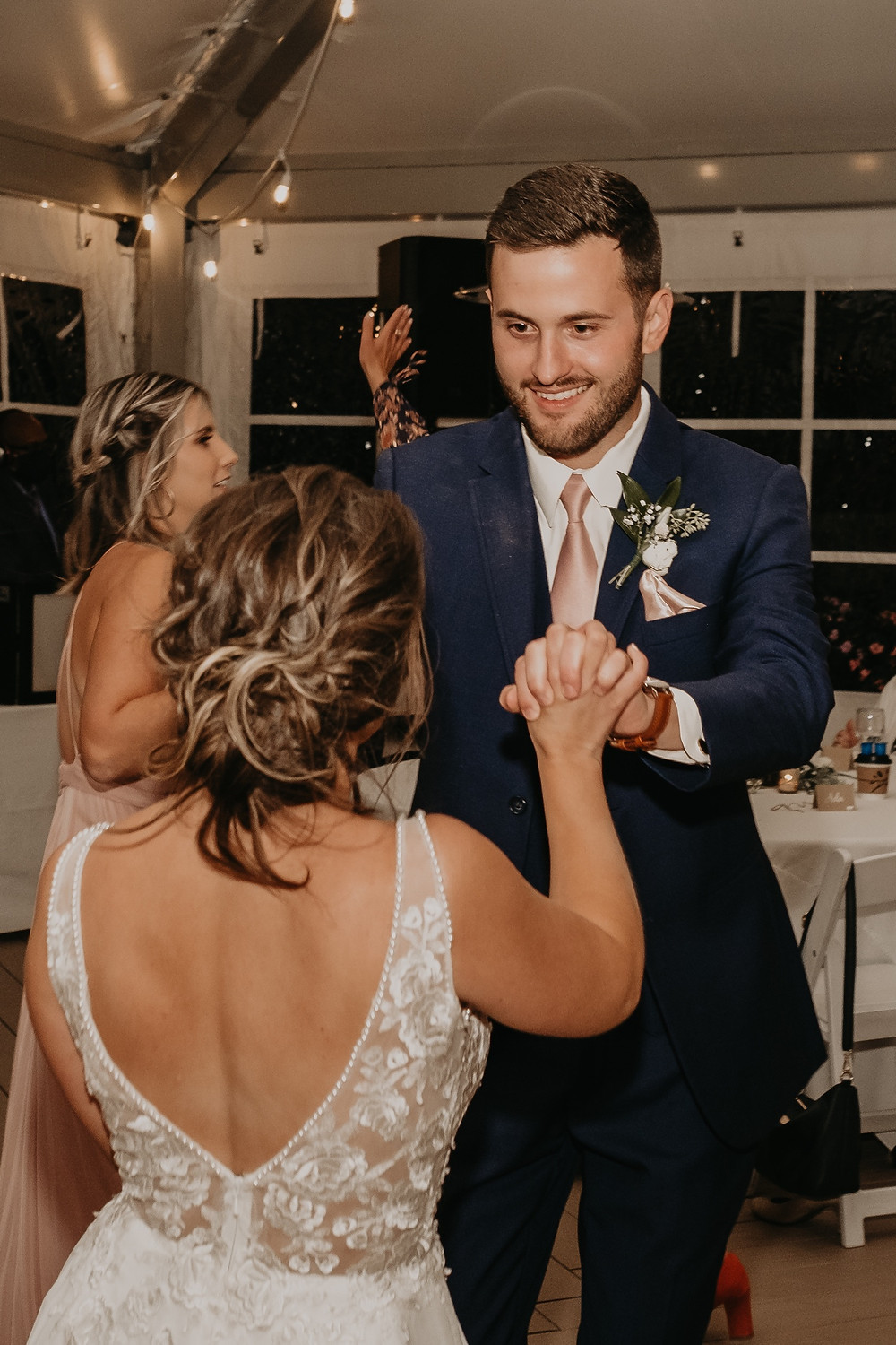 Family and guests dance at wedding with bride and groom. Photographed by Nicole Leanne Photography.