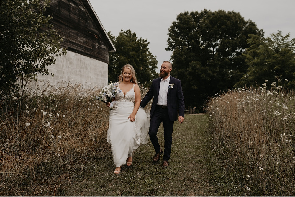 Bride and groom walking through field on wedding day. Photographed by Nicole Leanne Photography.