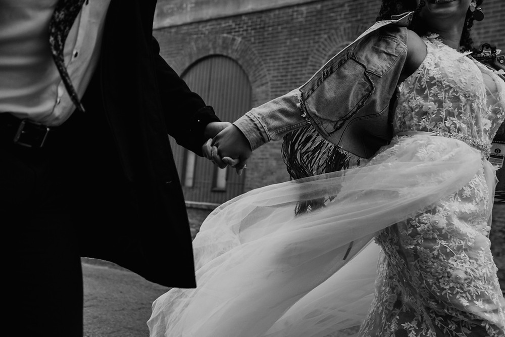 A couple holding hands walking in Detroit for wedding photos. Photographed by Nicole Leanne Photography.