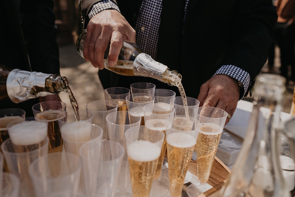 Pouring champagne into flutes at park wedding.