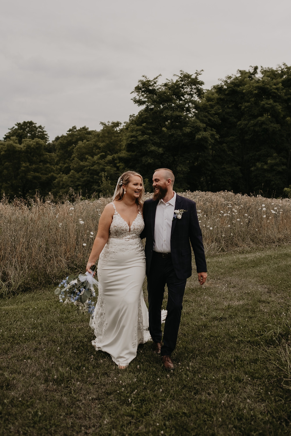 Bride and groom walking through field in Metro Detroit. Photographed by Nicole Leanne Photography.
